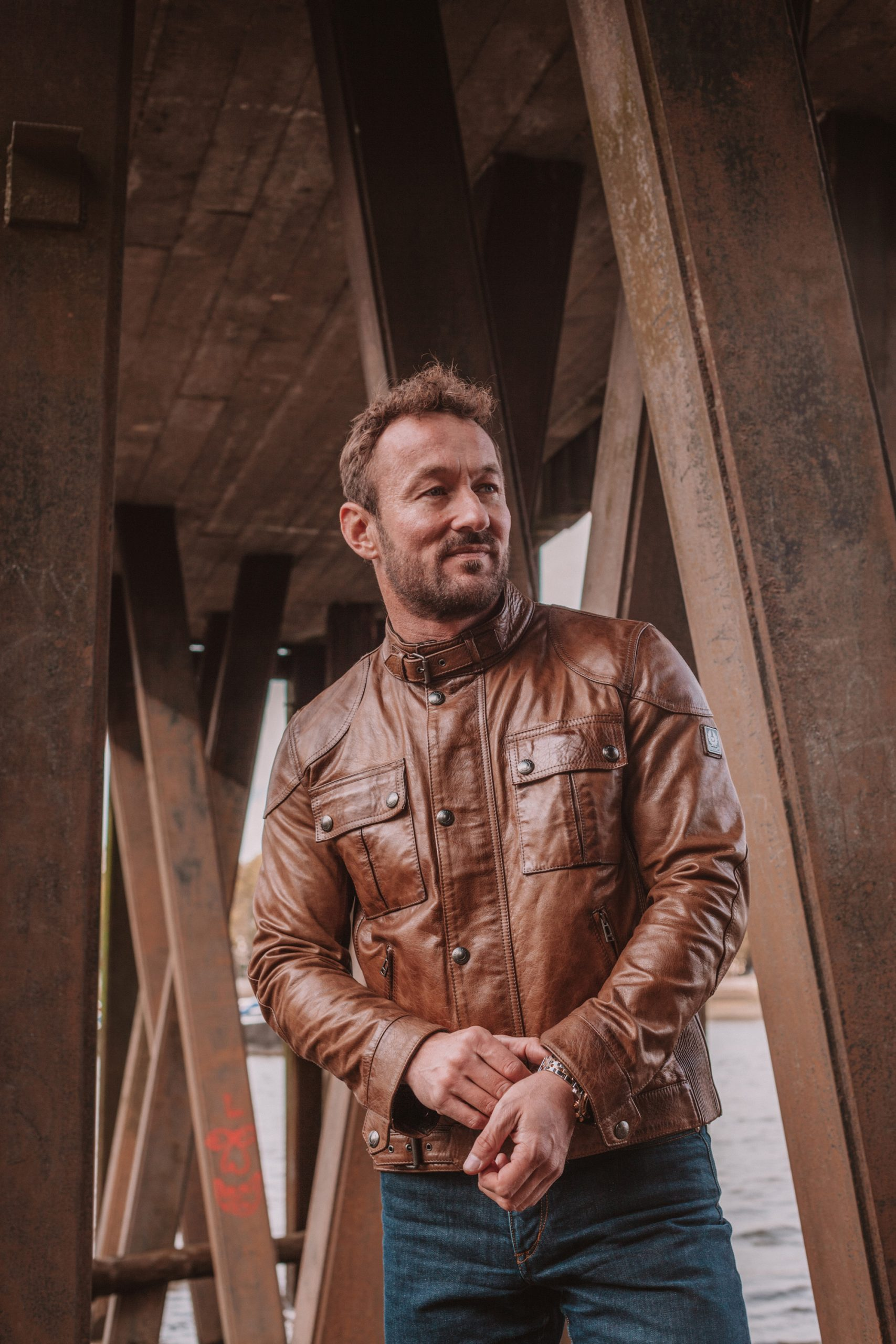 James Rostance wearing a leather jacket under a bridge