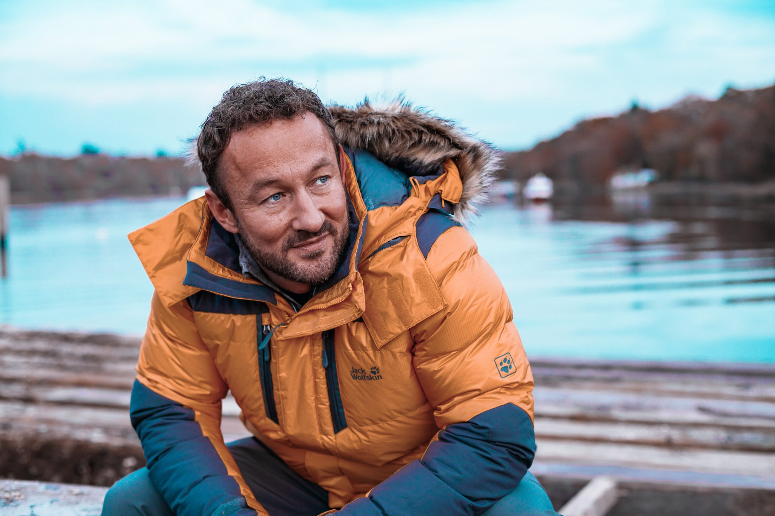 James Rostance sat on a log pile near the water in a yellow jacket